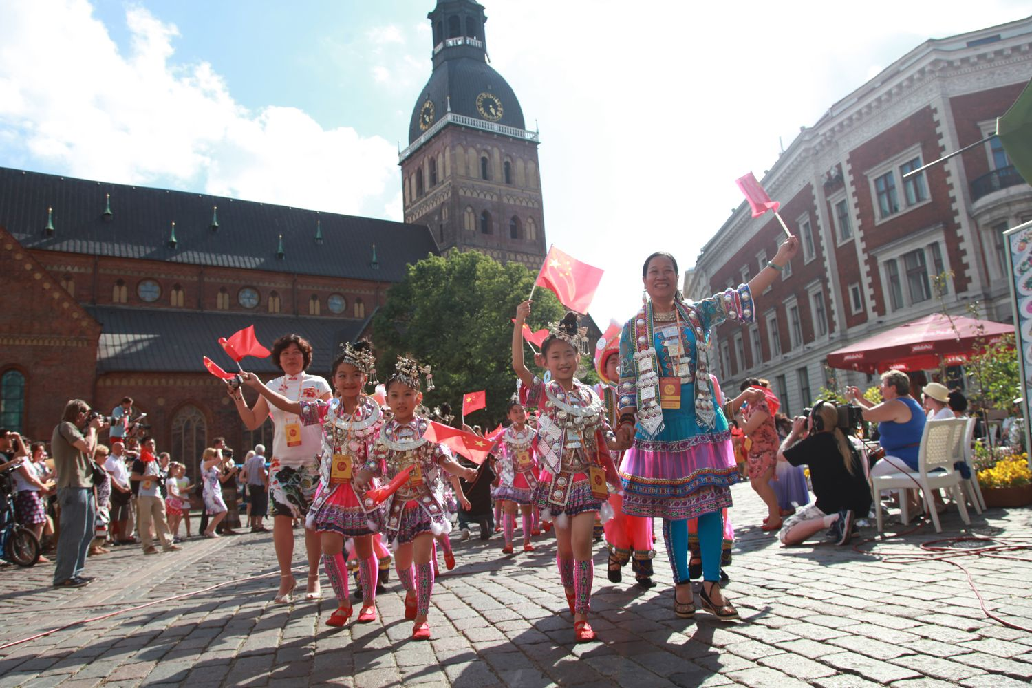 Chinese choir parades through Riga's old town, waving flags